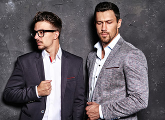 portrait of two sexy handsome fashion male models men dressed in elegant suits posing near dark  gray wall