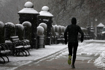 A man jogs during a snowstorm in upper Manhattan in New York City