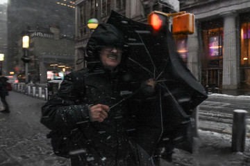 A man struggles with his umbrella during a nor'easter storm in New York City