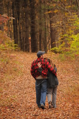 Young couple taking a walk through an Autumn forest