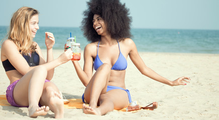 two multicultural  girl friends on beach vacation  smiling sitting on sand drinking cocktail.