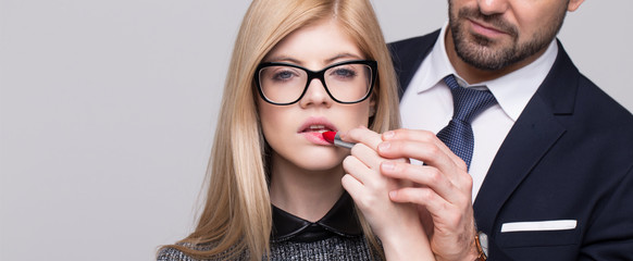 Stylish man hand helps apply red lipstick to blonde woman banner