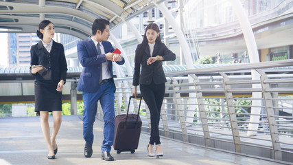 group smart business people of man and woman walk together in rush hour in feeling stress  with tablet smart phone device and luggage at the outdoor pedestrian walkway space in the morning.