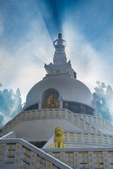 Japanese shanti-stupa, aka Peace pagoda, on the top of mountain in the Darjeeling, in a haze of the arising clouds.