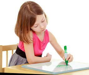 little girl draws with marker sitting at the table.