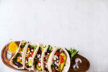 Mexican tacos with avocado, grilled corn, red cabbage slaw and chili salsa on wooden board black shale table. Recipe for Cinco de Mayo party. Top view. Copy space background