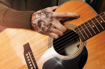 Closeup tattooed man holding acoustic guitar