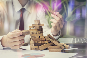 Closeup of Business hand playing wood blocks stack game