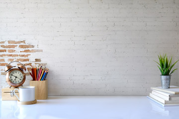 Front view of white desk with coffee mug and house plant. workspace and copy space