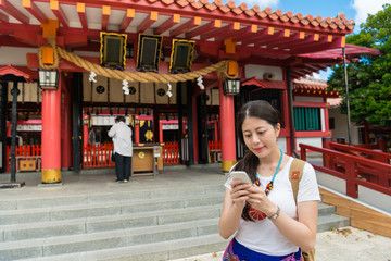 woman using the phone in  Naminoue Shrine sight.