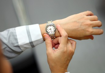 women looking at time on her wrist watch