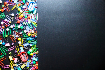 Top view of office table or desk with colorful equipment on black background with copy space for text.