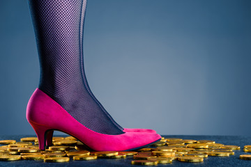 ピンクのヒールを履いた女性の足と散らばったお金