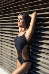 Young and sexy girl in a swimsuit posing outdoor.