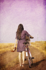girl walking down the road with bike