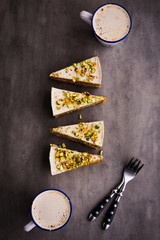 Raw vegan pistachio carrot cake with cashew cream layers from above on concrete table. Dark food photography styling concept. Vertical