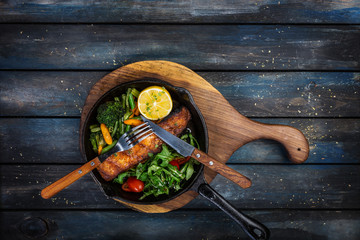 Grilled salmon fillet in a frying pan, vegetables, arugula with a lemon.