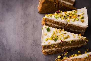 Raw vegan pistachio carrot cake with cashew cream layers from above on concrete table. Dark food photography styling concept.