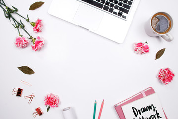 Woman workspace with laptop, handwritten quote notebook, pink carnation flower, coffee and stationery on white background. Flat lay, top view. stylish female blogger concept. pink  summer background.