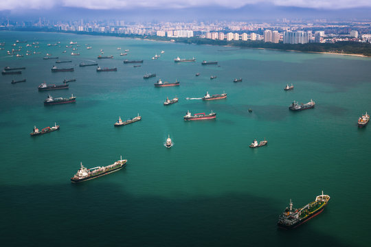 Top view from airplane of Singapore harbor with transportation boat and container ship