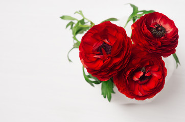 Rich red buttercup flowers in vase on soft white wooden table, top view. Elegance bouquet for modern interior.
