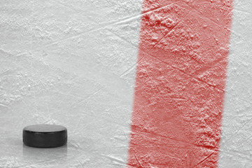 Puck and fragment of the ice arena with a red line