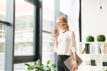 Cheerful young business woman holding laptop computer looking aside drinking coffee.
