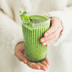 Matcha green vegan smoothie with chia seeds and mint in glass in hands of female wearing white sweater, square crop. Clean eating, detox, alkaline diet, weight loss food concept