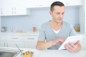 attractive man standing and using tablet on the kitchen