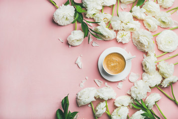 Spring morning concept. Flat-lay of cup of coffee surrounded with white ranunculus flowers over light pink background, top view, copy space, horizontal composition