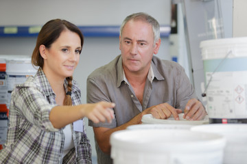 friendly couple choosing paint bucket in housewares hypermarket