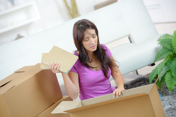 happy young woman opening a carton box