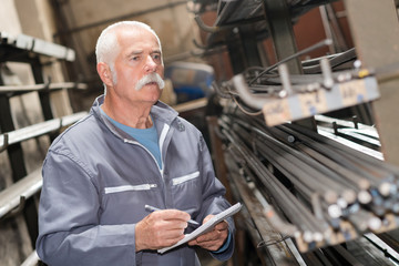 senior worker counting metal bars in warehouse