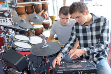 Young men with electronic drumkit and amp