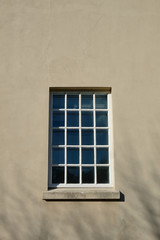 Big square window with small glazing pattern made of many mullions in a plastered building facade
