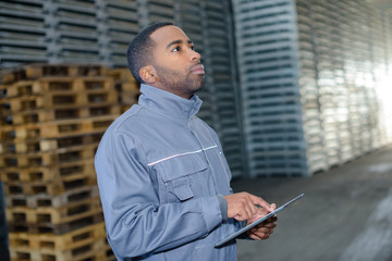 Man in warehouse holding tablet computer