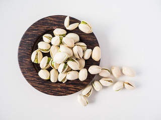 Pistachios closeup on wooden plate and white background.