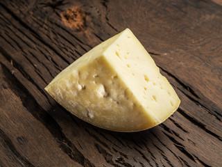 Piece of homemade cheese on the wooden background.
