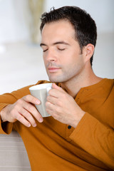 young man enjoying tea with closed eyes