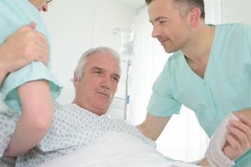 caretaker helping senior patient in bed