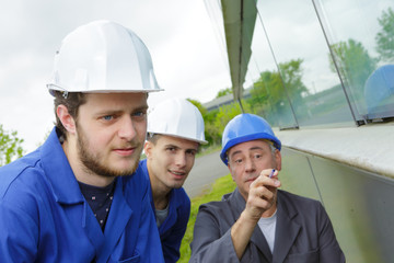 apprentices being shown detail on outside of building