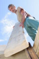 Upward view of man holding plank of wood