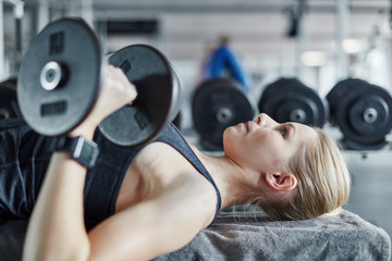 Young woman doing weight training exercise with dumbbells in the gym