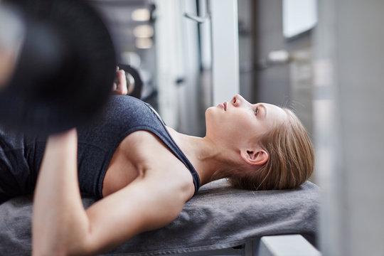 Junge Frau trainiert Kraft und Brustmuskeln