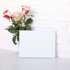 Mockup poster frame. White blank canvas and roses. Pink brick wall on background.