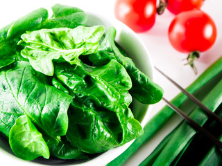 Little branch of cherry tomatoes, bowl of spinach, green hot peppers,onion leaves, garlic and fork over white isolated background.