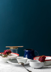 Various dishes on a white table near a blue wall..
