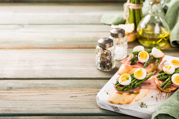 Easter breakfast or lunch with sendwich with ham, asparagus and quail eggs on white old chopping board on wooden background. Spring food concept with copy space.