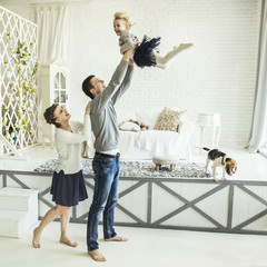 loving parents play with their young daughter