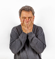 astonished anxious man has hands in the face